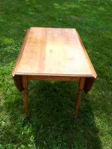 Wooden dining table with folding sides.
