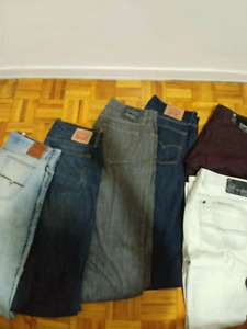 Assortment of GUESS, BUFFALO, LEVI jeans for sale.