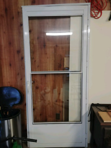 Storm door with roll away screen