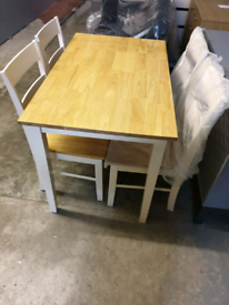 A new stylish 2 tone dining table with four chairs .