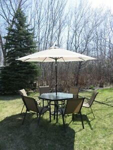 Glass patio set with 6 chairs and umbrella. Asking $350.00