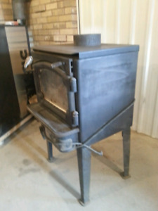 Wood stove with blower fan and cert tag.