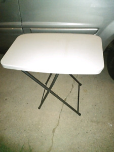 Plastic folding table with metal legs.