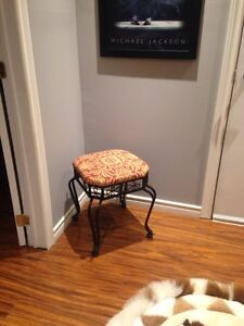 Black ornate metal seat with orange and beige floral pad