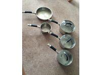 Set of Antony Worrall Thompson induction hob pans.