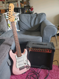 3/4 size baby-pink, strat-style guitar with amp