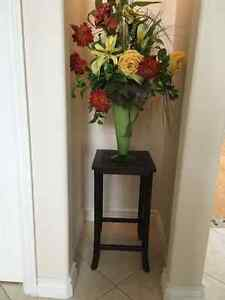 Three small occasional tables and floral arrangements