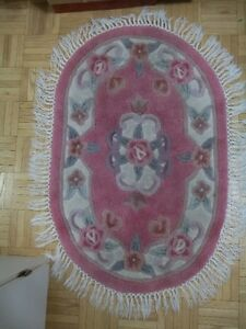 pink area rug with a white fringe