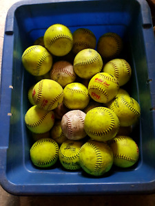 Bin full of softballs mostly hot dots and gold dots some are new