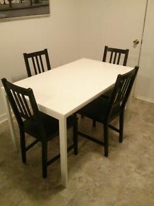 Table blanche avec 4 chaises noires