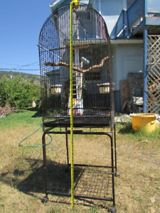 Big bird cage on casters w/ perches, toys, etc.