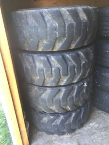 For Sale a set of four Skid Steer tires mounted on rims.
