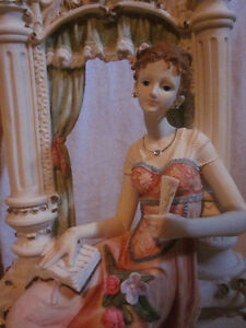 Figurine of Woman sitting by Window Sill w/ Flowers and a Book
