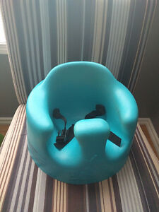 Blue bumbo seat with safety straps