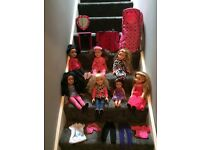 Designer doll bundle. 7 dolls, spare clothes, dressing table, wardrobe and a carry case