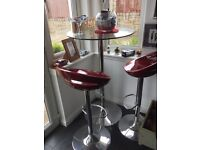 Bistro style glass table with two red gas powered multi height chairs