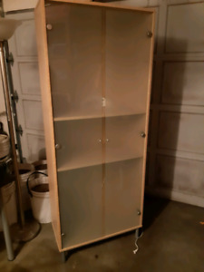 Blonde IKEA hutch with glass doors.