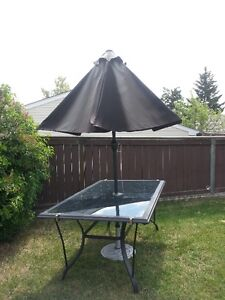 Like new Glass patio table with umbrellor and base