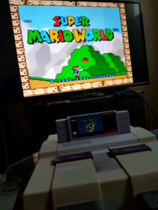 Super Nintendo with 2 controllers and super mario world
