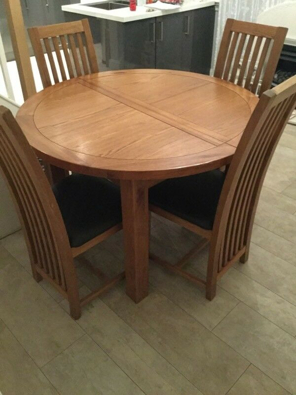 Solid oak extending round dining table and four chairs