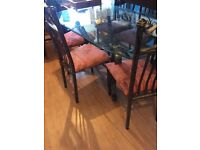Glass table and six iron chairs for sale