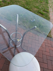 Glass dinning table and four white lether chairs