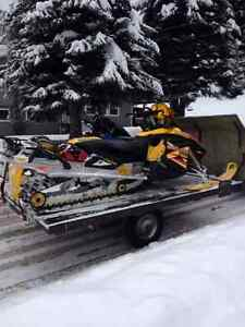 2 skidoos and  tilting deck trailer
