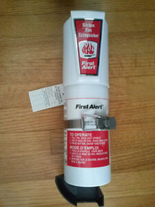 NEW AND UNUSED KITCHEN FIRE EXTINGUISHER IN MOUNTING BRACKET