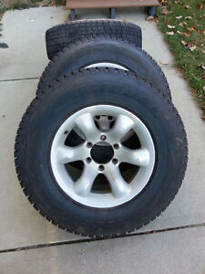 Four P235/75R16 Bridgestone Blizzak winter tires on rims