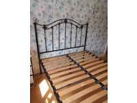 Double (4ft 6in) metal bed frame, black finish, with 2 central support legs and sprung wooden slats.