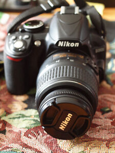 Nikon D3100 with 18-55 mm lens, 2 batteries, charger and case