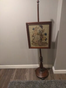 Antique fire screen with needle point frame.