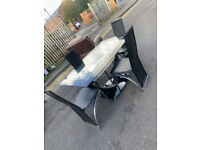 58. Black glass table and 4 leather chairs