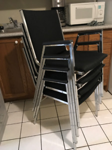 4 black stacking chairs