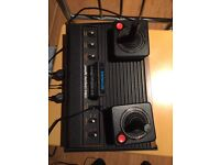 Boxed Atari 2600 (woody 6 button version) with 2 joysticks and 2 paddles.