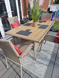 Large biscuit coloured rattan dining table with 4 stackable chairs
