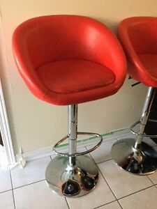 A pair of beautiful red Leather swivel chairs.