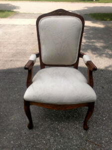 Antique wood chair with white upholstery.