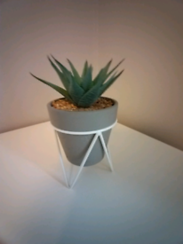 Faux cactus plant in stand