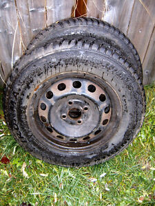 A PAIR OF SNOW TIRES MOUNTED ON RIMS