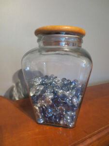 Pot en verre avec roches décoratives bleu et transparente.