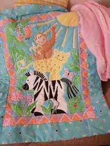 Blue jungle crib comforter and pink fitted crib sheet