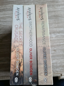 Three assassin's creed books, still in the plastic