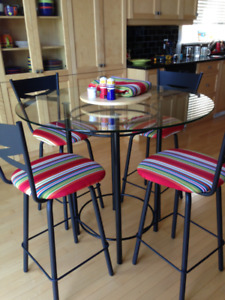Glass dining table with metal base and six matching bar stools