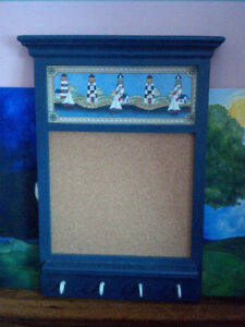 Corkboard in a blue wooden frame with lighthouse art