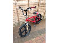 Red bmx bike with stunt pegs