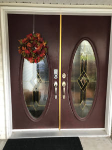 Two Used Exterior Doors with Oval Glass Inserts.