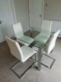 Square glass table and four cream faux leather chairs