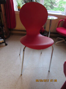 Two red chairs with chrome legs.
