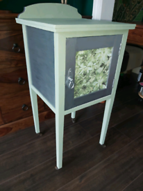 Green and silver cabinet on wheels with succulent detail